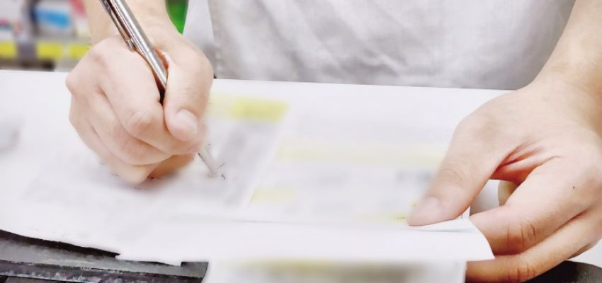 close-up-of-a-pharmacist-writing-and-filling-out-prescription-forms-before-entering-patient-info-into_t20_W7070m