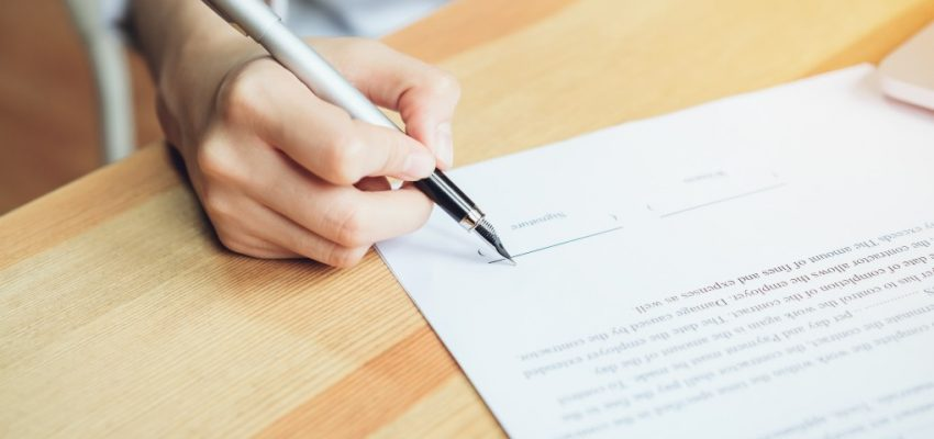 closeup-of-signing-a-documentation-agreement-and-pen-on-the-table_t20_bAoa8P