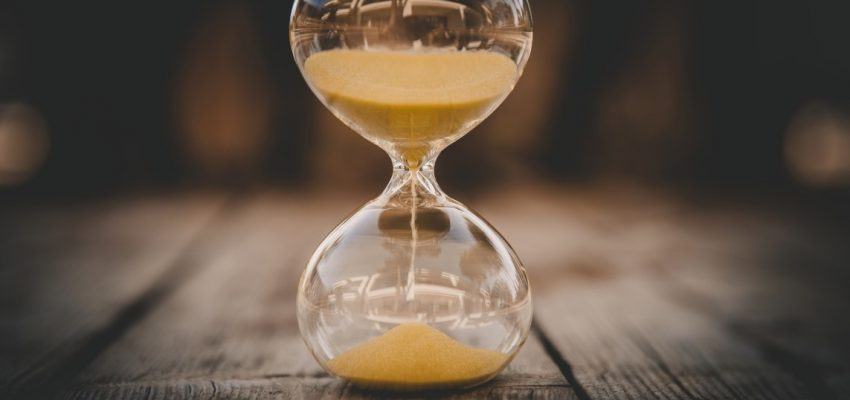 hourglass-with-falling-grains-of-sand-on-a-wooden-background-summer-time-concept-of-time-passing_t20_QK27YE