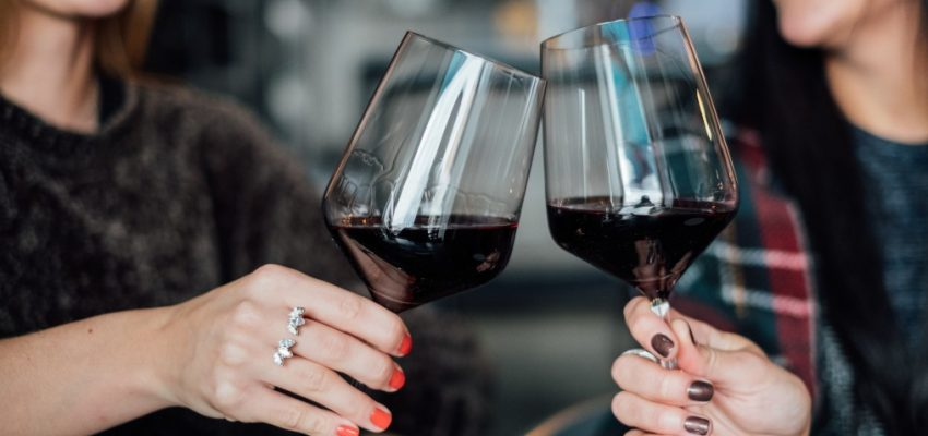 two-happy-woman-holding-glass-of-red-wine_t20_JYVXpP
